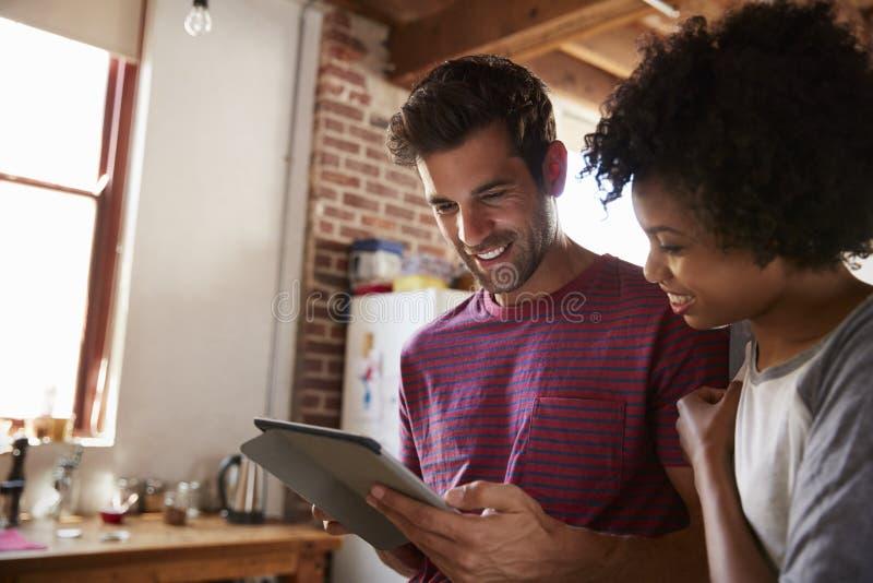 Het jonge gemengde raspaar die tablet in keuken gebruiken, sluit omhoog stock fotografie