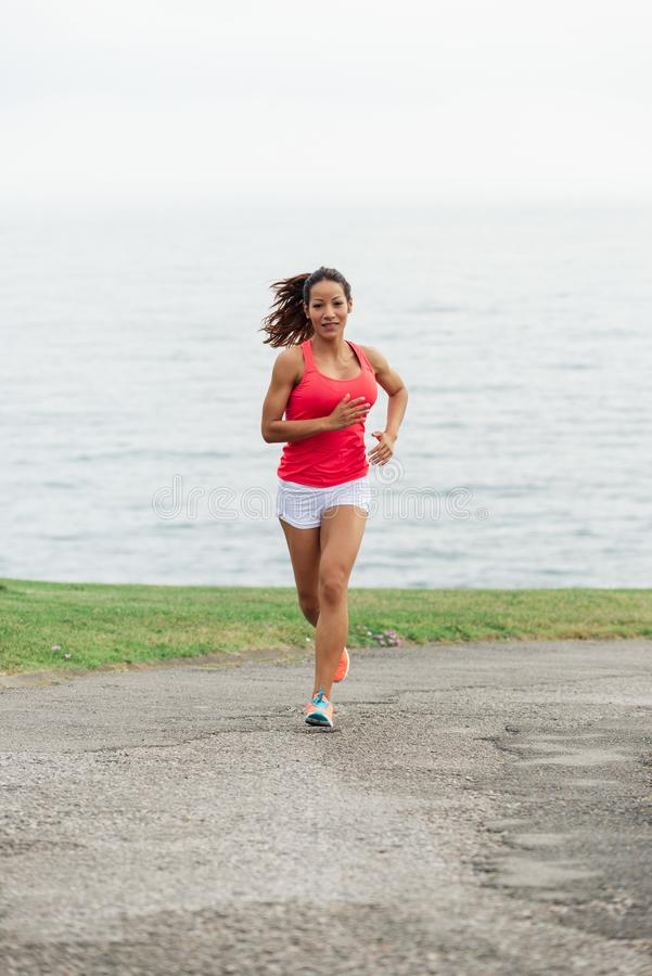 Het jonge geschikte Latijnse vrouwelijke atleet lopen stock foto