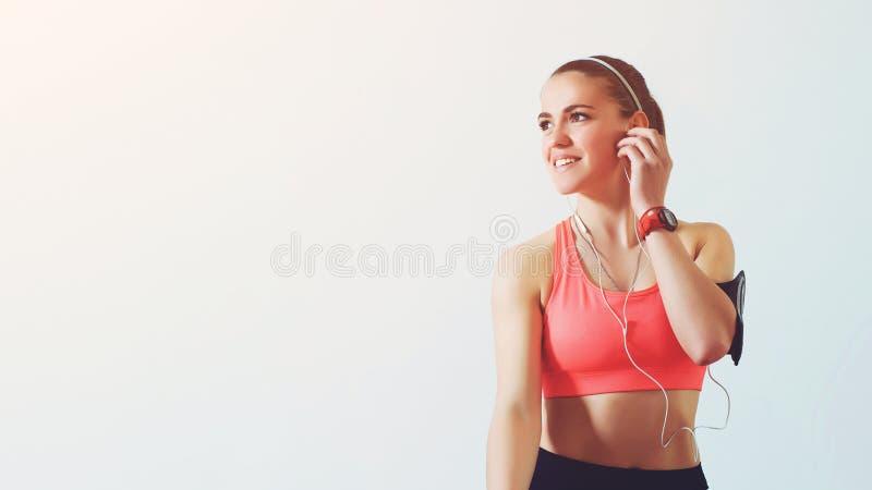 Het jonge geschiktheidsvrouw opzij kijken, luistert muziek terwijl het nemen van een onderbreking Actief meisje die smartphone in stock afbeelding