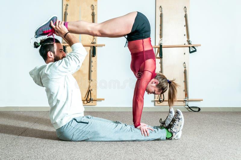 Het jonge gezonde acrobatische paar die van de yogageschiktheid pret in de gymnastiek hebben die en grappige acrobaat uitvoeren u royalty-vrije stock foto's