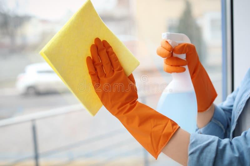 Het jonge glas van het vrouwen schoonmakende venster thuis stock foto's