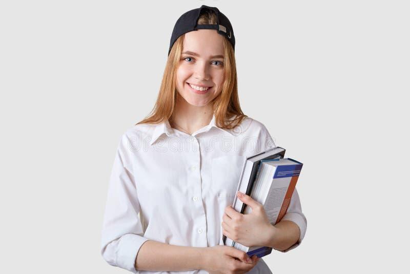 Het jonge het glimlachen student stellen over een witte achtergrond met bos van kleurrijke boeken, kijkt gelukkig en tevreden Eer stock fotografie