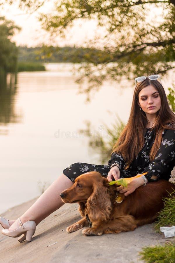 Het jonge het glimlachen vrouw spelen met haar hond in de tuin, knuffelt zij haar huisdier stock afbeelding