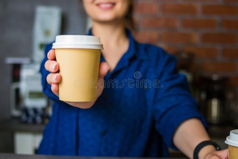 het jonge glimlachende baristameisje houdt haar hand met een document kop van koffie stand royalty-vrije stock foto's
