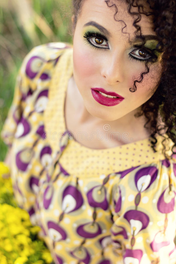 Het jonge glimlachende meisje in een zonnige de zomerdag met krullen en mooie make-up bekijkt de hemel royalty-vrije stock foto's