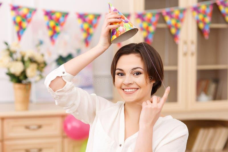 Het jonge glimlachende meisje probeert op haar partijhoed royalty-vrije stock foto's