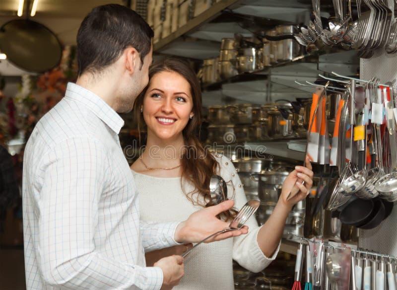 Het jonge glimlachende paar kiest kokende werktuigen stock foto's
