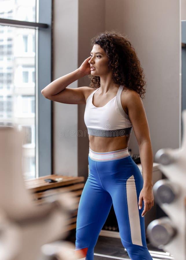 Het jonge goede geschikte krullende meisje gekleed in sportenkleren bevindt zich naast de sportuitrusting in de moderne gymnastie royalty-vrije stock afbeeldingen