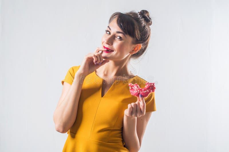 Het jonge grappige donkerbruine model met donuts die studio stellen schoot op witte geïsoleerde niet achtergrond, royalty-vrije stock fotografie