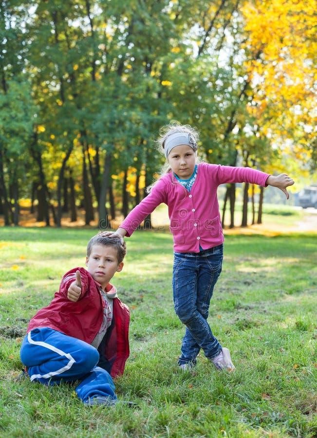 Het jonge gras van de jongenszitting, die duim en mooie meisjesdreun neer in de herfstpark tonen royalty-vrije stock afbeelding