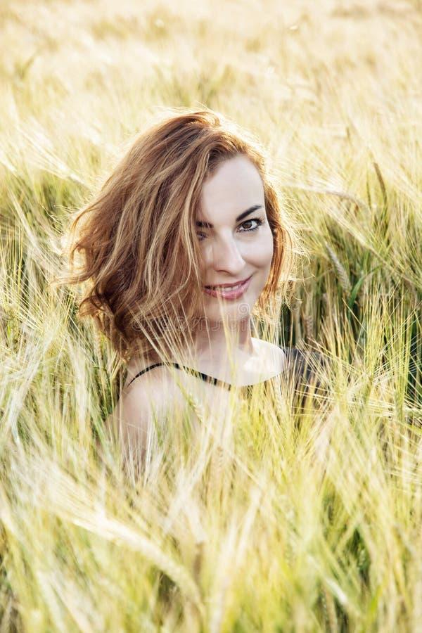 Het jonge het glimlachen vrouw stellen in het de de tarwegebied, schoonheid en aard stock afbeelding