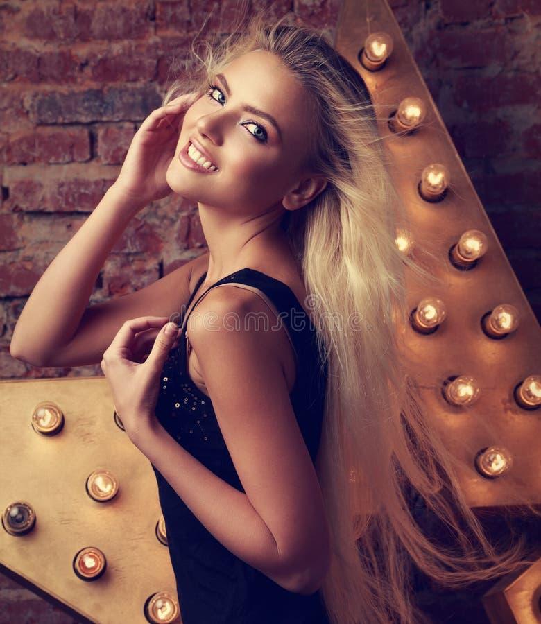 Het jonge het glimlachen vrouw stellen met lang blond haar op ster en bric stock afbeelding