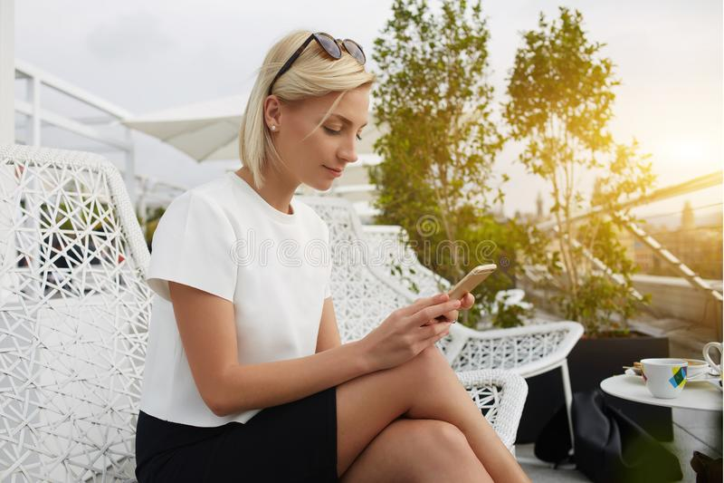 Het jonge hipstermeisje babbelt in sociaal netwerk via mobiele telefoon, terwijl in koffie ontspant royalty-vrije stock foto