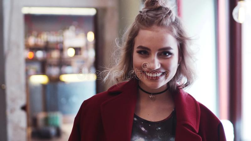 Het jonge hipstermeisje met toevallige uitrusting kijkt net in de camera en glimlacht gelukkig Modieus kijk, rode laag, lichte ma