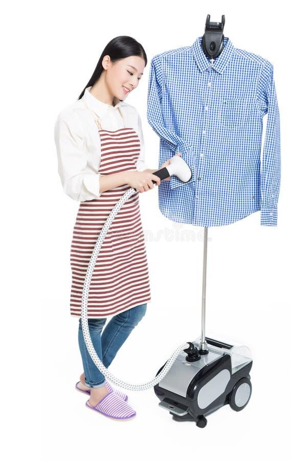 Het jonge huisvrouw strijken stock afbeelding