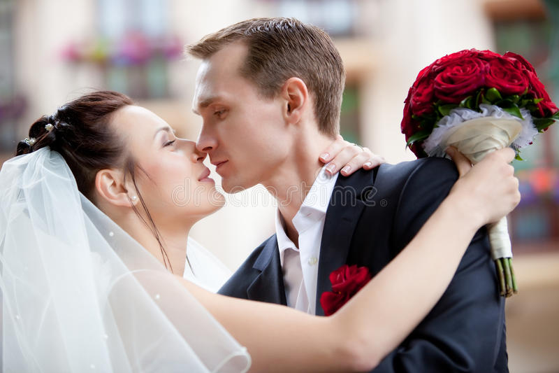 Het jonge huwelijkspaar kussen stock afbeelding