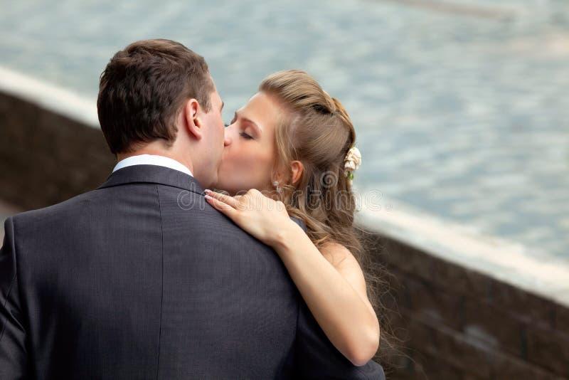 Het jonge huwelijkspaar kussen royalty-vrije stock foto's