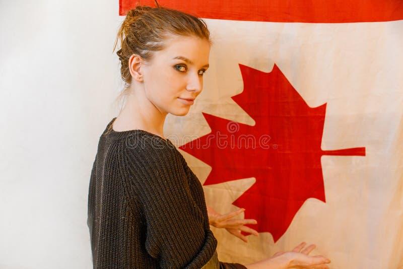 Het jonge immigrantenmeisje in zwarte trui kijkt het achter stellen voor beeld van de de vlag het uitstekende kleur van Canada stock foto