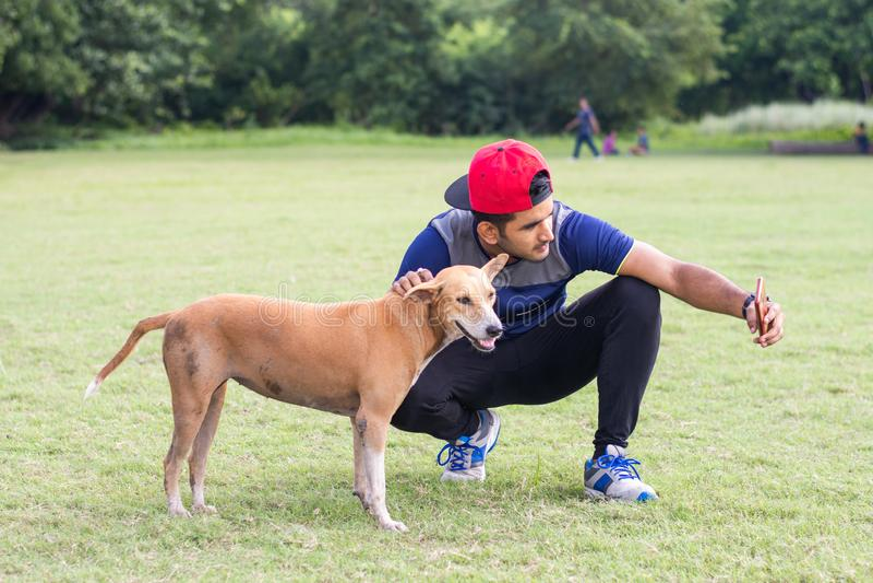 Het jonge Indische atletenmens spelen met hond en het nemen selfies in sportengrond terwijl het aanstoten Mannelijke Sporten en f stock foto