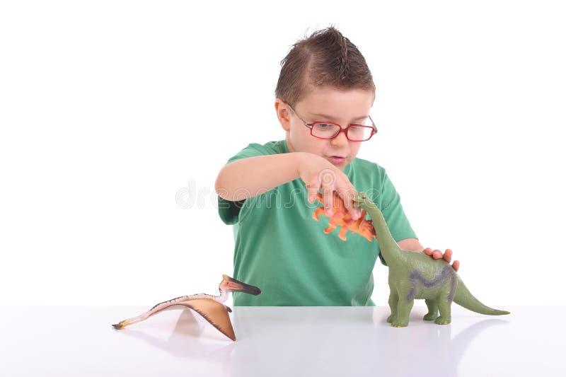 Het jonge jong geitje spelen met dinosaurussen stock afbeeldingen