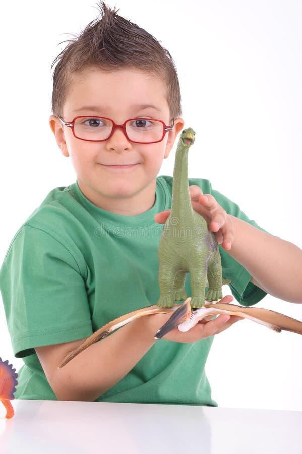 Het jonge jong geitje spelen met dinosaurussen stock afbeelding