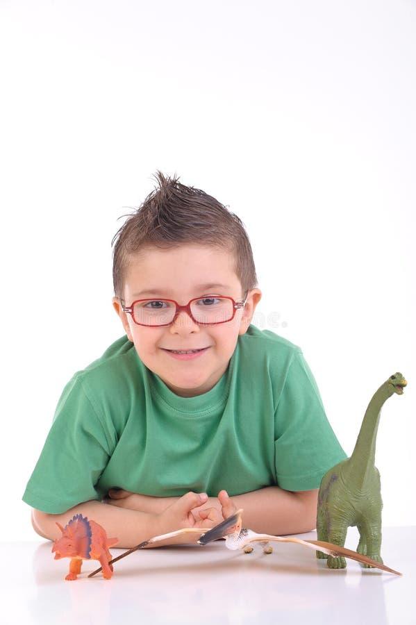 Het jonge jong geitje spelen met dinosaurussen royalty-vrije stock foto's
