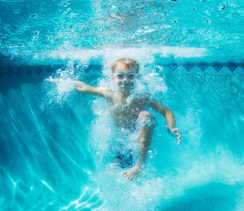 Het jonge Jongen Duiken Onderwater in Zwembad stock afbeelding