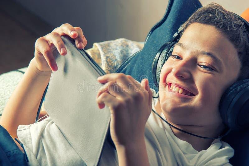 Het jonge jongen liggen die aan muziek luisteren of heeft een e-lerende klasse op zijn tabletcomputer in bijlage aan een paar hoo stock afbeeldingen