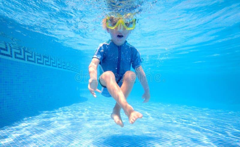 Het jonge jongen onderwater spelen stock afbeelding