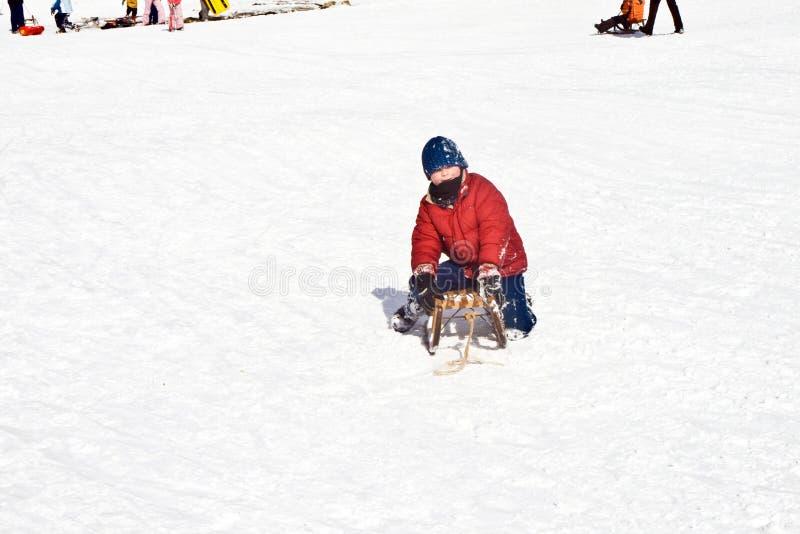 Het jonge jongen sledding onderaan de heuvel in sneeuw, de witte winter stock foto's