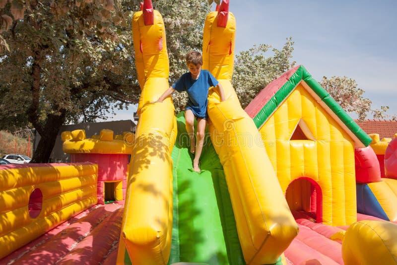 Het jonge jongen spelen in een opblaasbaar stuk speelgoed huis in een park stock fotografie