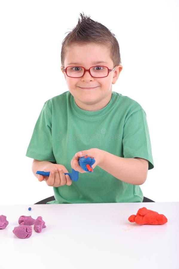 Het jonge jongen spelen met modelleringsklei stock foto's