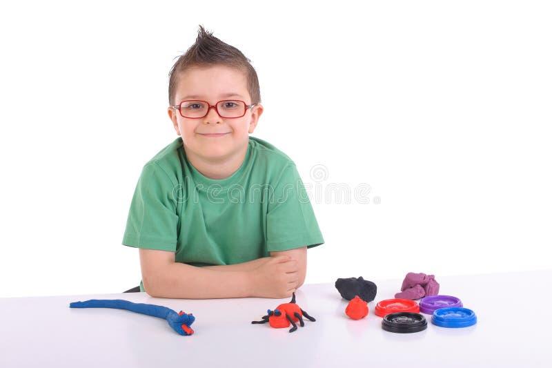 Het jonge jongen spelen met modelleringsklei royalty-vrije stock foto