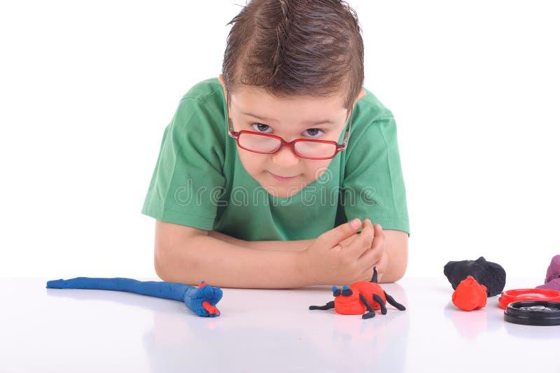 Het jonge jongen spelen met modelleringsklei stock foto
