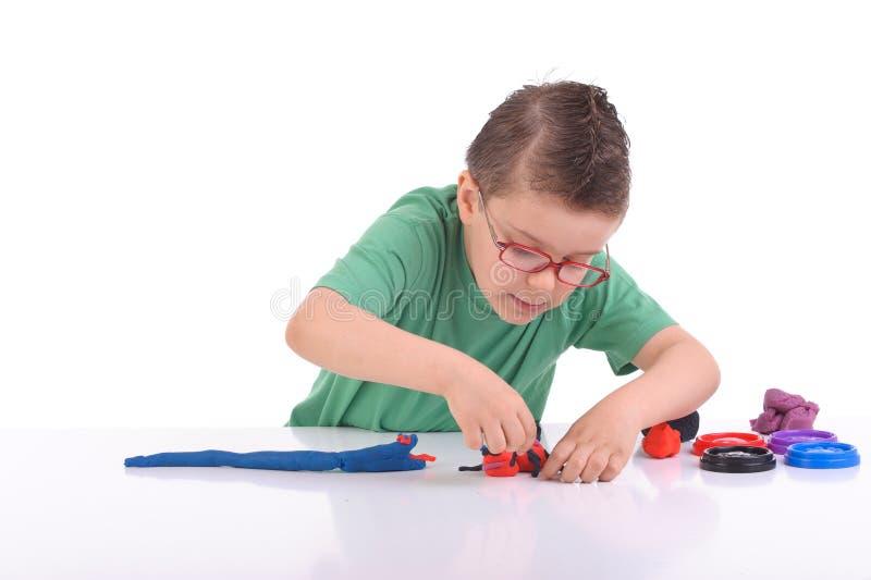 Het jonge jongen spelen met modelleringsklei royalty-vrije stock afbeeldingen