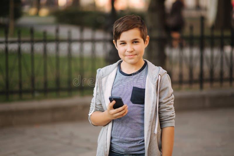 Het jonge jongen spelen met smaptphone Schooljongen die mobiele telefoon op de straat met behulp van stock afbeeldingen