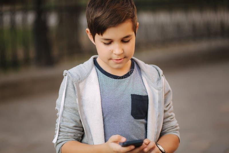 Het jonge jongen spelen met smaptphone Schooljongen die mobiele telefoon op de straat met behulp van stock fotografie