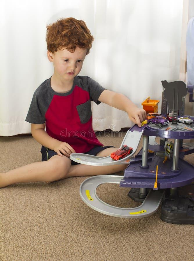 Het jonge jongen spelen met stuk speelgoed auto's stock foto's