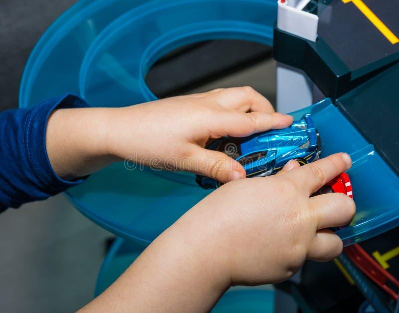 Het jonge jongen spelen met uitstekende stuk speelgoed auto's thuis Selectieve nadruk op hand van jongen en stuk speelgoed stock foto