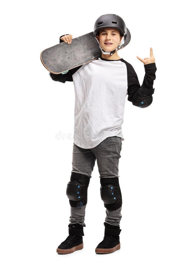 Het jonge jongen stellen met een skateboard en een gesturing rots - en - broodje stock foto's