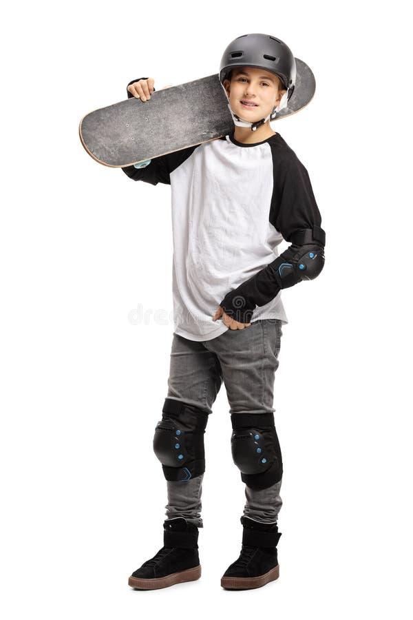 Het jonge jongen stellen met een skateboard op zijn schouder en een helm stock afbeeldingen