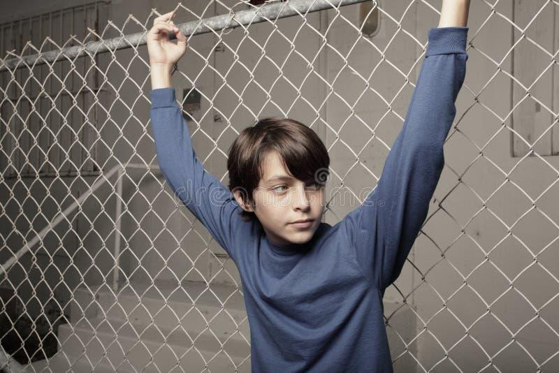Het jonge jongen stellen op een ketting-verbinding omheining stock fotografie
