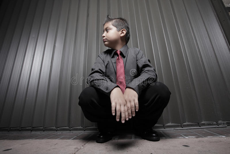 Het jonge jongenszakenman hurken royalty-vrije stock afbeeldingen