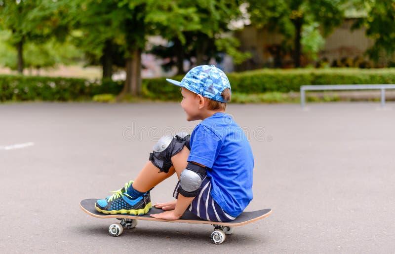 Het jonge jongenszitting letten op op zijn skateboard stock foto's
