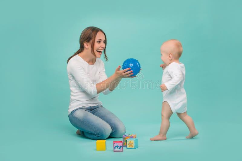 Het jonge Kaukasische aantrekkelijke het glimlachen moeder spelen stock afbeeldingen
