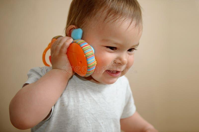 Het jonge Kaukasische babymeisje spreken op een stuk speelgoed het exemplaarruimte van de celtelefoon, sluit omhoog portret royalty-vrije stock foto