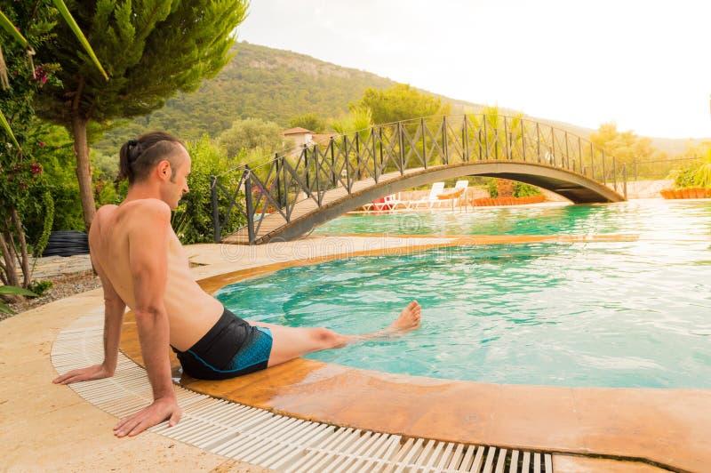 Het jonge Kaukasische mens ontspannen dichtbij zwembad in een toevlucht royalty-vrije stock afbeelding