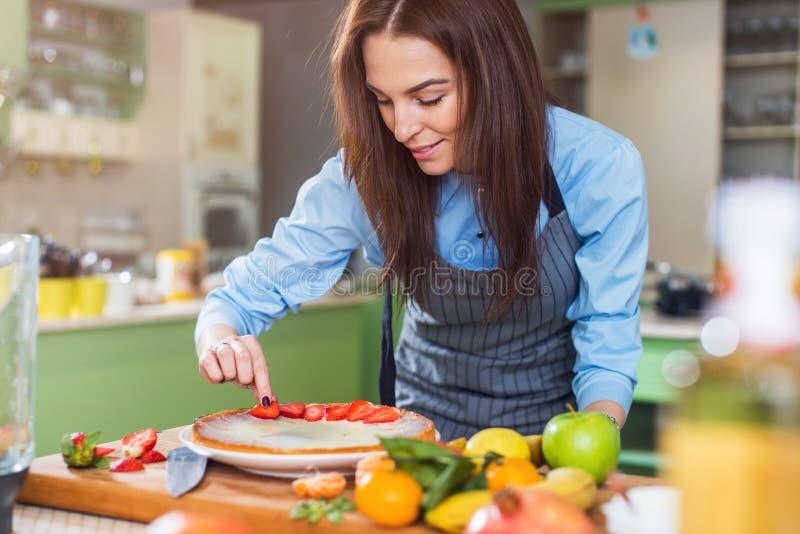Het jonge Kaukasische vrouw koken in de keuken, makend een cake, die het verfraaien met aardbei stock afbeeldingen