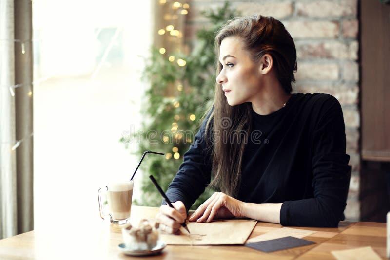 Het jonge Kaukasische vrouw werken, die in een restaurant schrijven Zaken royalty-vrije stock afbeelding