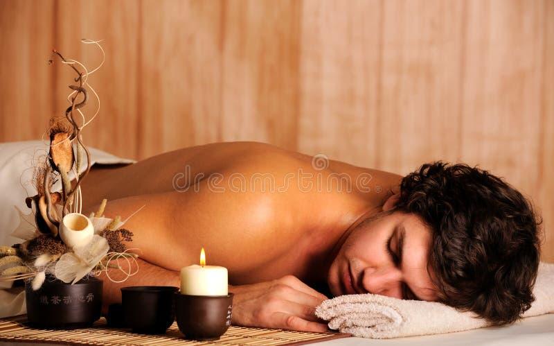 Het jonge knappe mens ontspannen in kuuroordsalon stock afbeeldingen